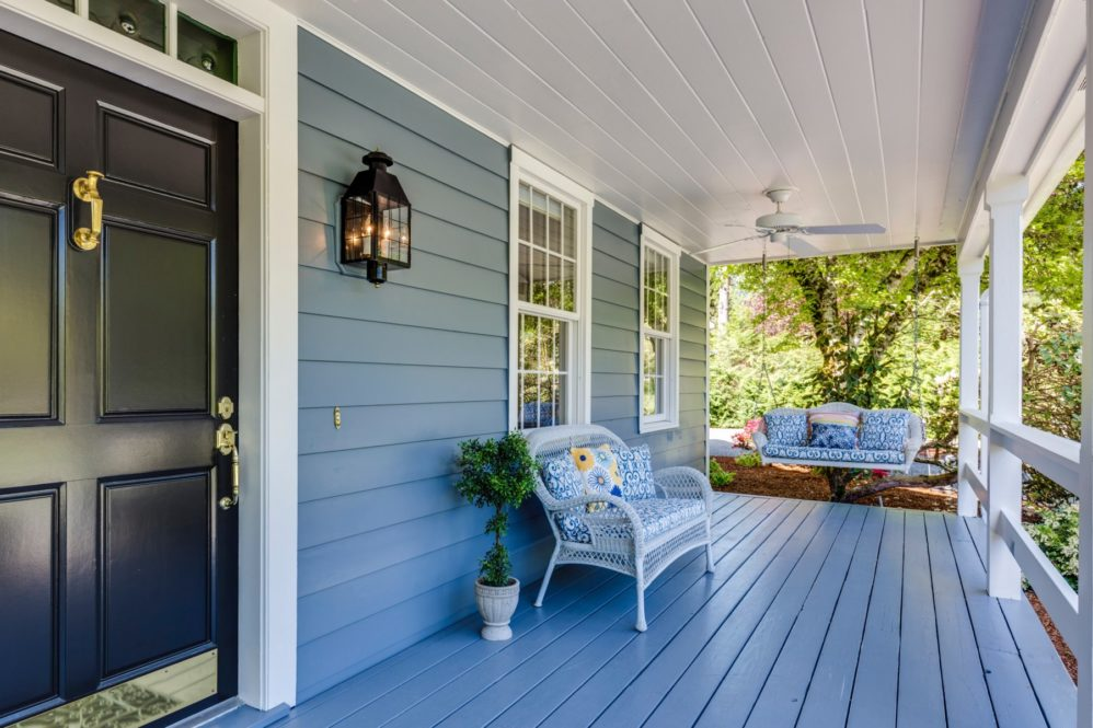 porch on house with blue siding in summer